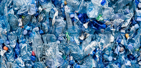 Large pile of discarded plastic bottles in a landfill.