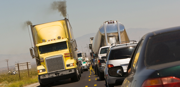 Shipping truck billowing smoke on a packed roadway.